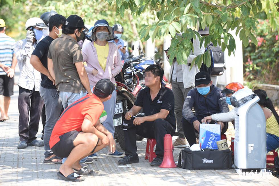Người dân tìm cách ném hàng qua hàng rào bất chấp lệnh ngưng tiếp tế - Ảnh 14.
