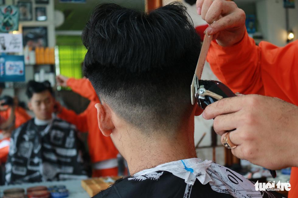 Tiệm cắt tóc giá 2.000 đồng của những anh thợ áo cam - Ảnh 3.