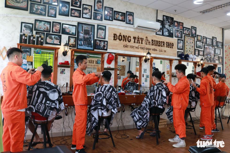 Tiệm cắt tóc giá 2.000 đồng của những anh thợ áo cam - Ảnh 1.
