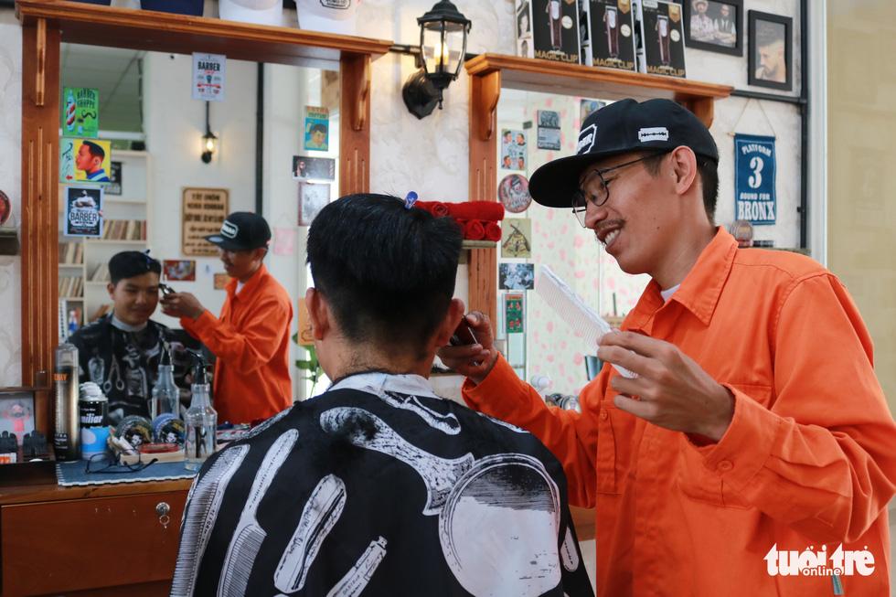 Tiệm cắt tóc giá 2.000 đồng của những anh thợ áo cam - Ảnh 2.