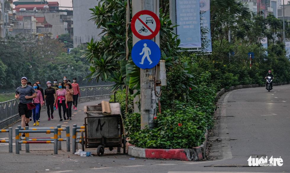 Công viên đóng cửa, nhiều người dân Hà Nội liều mình ra đường tập thể dục - Ảnh 8.