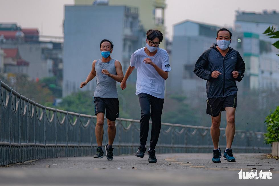 Công viên đóng cửa, nhiều người dân Hà Nội liều mình ra đường tập thể dục - Ảnh 4.