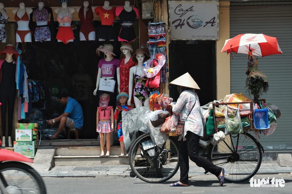 Người Hà Nội nhọc nhằn mưu sinh giữa nắng trên đầu đổ xuống, nóng từ mặt đường bốc lên - Ảnh 7.
