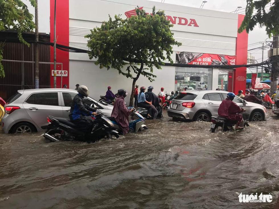 TP.HCM mưa gió mù mịt 2 tiếng: đường ngập khắp nơi, cây đổ, xe ngã... - Ảnh 7.