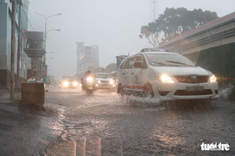 TP.HCM mưa gió mù mịt 2 tiếng: đường ngập khắp nơi, cây đổ, xe ngã... - Ảnh 10.