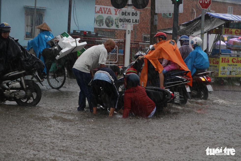 TP.HCM mưa gió mù mịt 2 tiếng: đường ngập khắp nơi, cây đổ, xe ngã... - Ảnh 11.