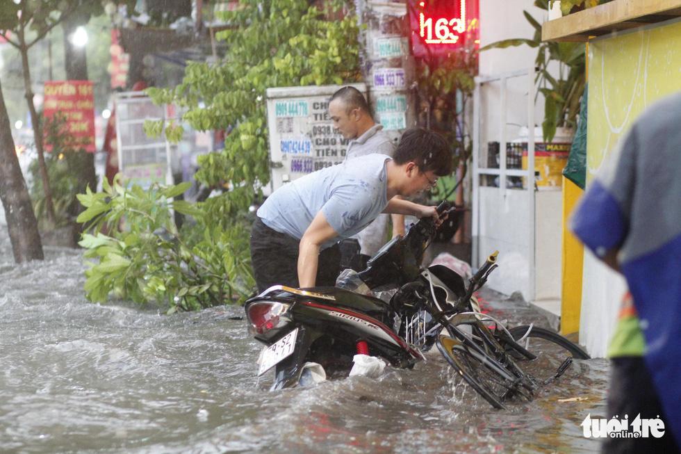 TP.HCM mưa gió mù mịt 2 tiếng: đường ngập khắp nơi, cây đổ, xe ngã... - Ảnh 2.