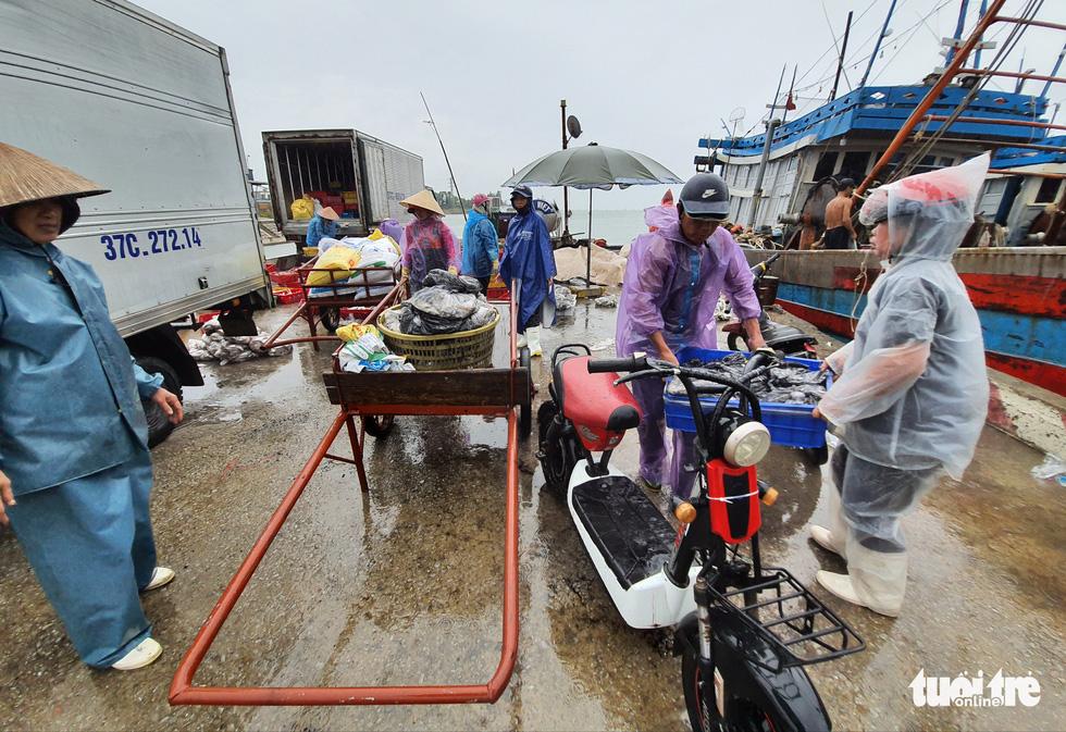 Ngư dân hối hả đưa hải sản vào bờ tránh bão số 2 - Ảnh 8.