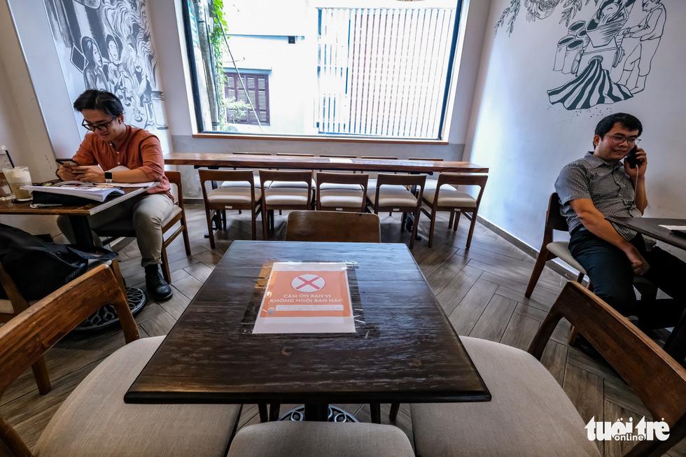 Quán bia, cà phê ở Hà Nội kê lại bàn ghế, ngồi cách nhau cả mét - Ảnh 1.