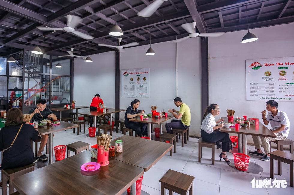 Quán bia, cà phê ở Hà Nội kê lại bàn ghế, ngồi cách nhau cả mét - Ảnh 9.
