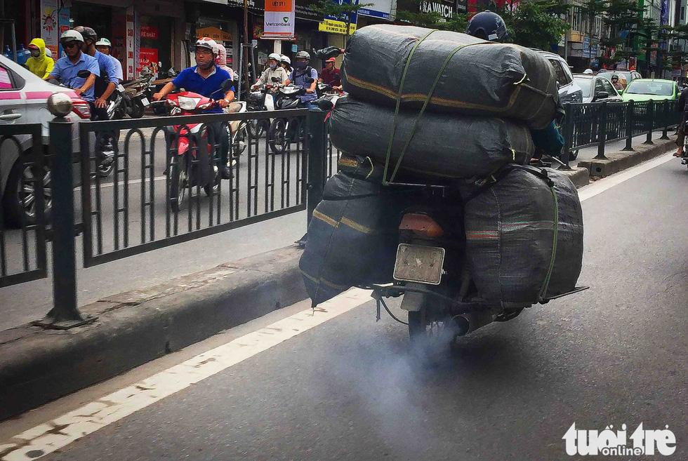 Xe máy phế liệu nhả khói đen, chở hàng cồng kềnh trên phố Hà Nội - Ảnh 1.