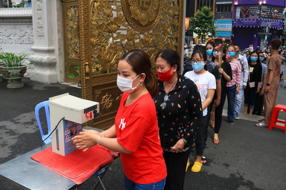 Chùa ở TP.HCM trang bị máy rửa tay, phát khẩu trang cho người đi viếng lễ Vu lan - Ảnh 2.