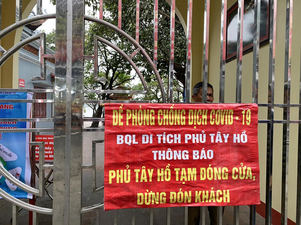 Đền chùa Hà Nội đóng cửa, người hành hương vái vọng, nhét tiền qua khe cổng - Ảnh 2.