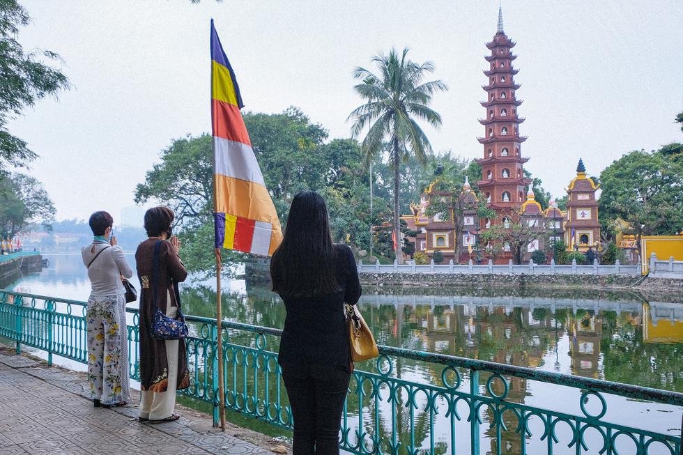 Đền chùa Hà Nội đóng cửa, người hành hương vái vọng, nhét tiền qua khe cổng - Ảnh 6.