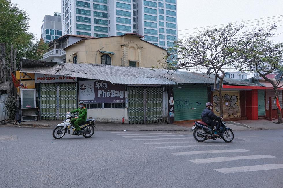 Đền chùa Hà Nội đóng cửa, người hành hương vái vọng, nhét tiền qua khe cổng - Ảnh 7.