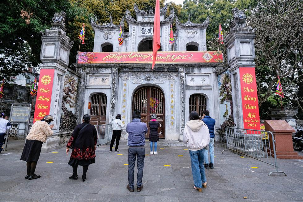Đền chùa Hà Nội đóng cửa, người hành hương vái vọng, nhét tiền qua khe cổng - Ảnh 3.