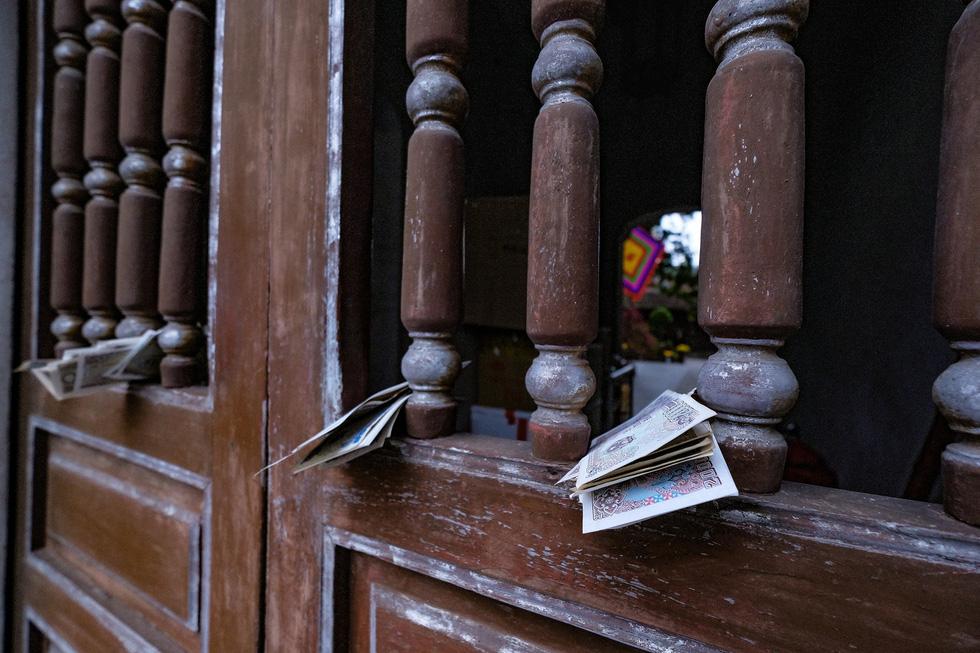 Đền chùa Hà Nội đóng cửa, người hành hương vái vọng, nhét tiền qua khe cổng - Ảnh 4.