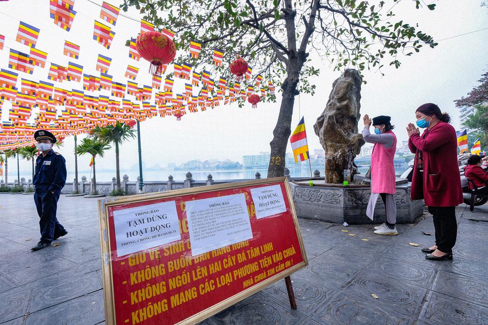 Đền chùa Hà Nội đóng cửa, người hành hương vái vọng, nhét tiền qua khe cổng - Ảnh 1.
