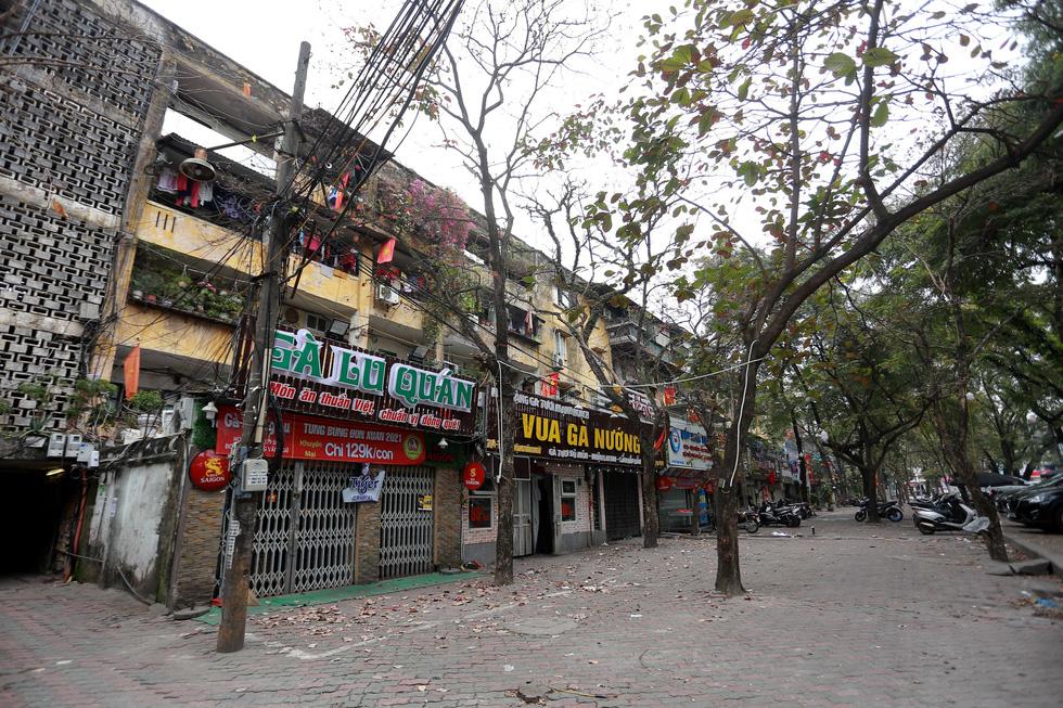 Đền chùa Hà Nội đóng cửa, người hành hương vái vọng, nhét tiền qua khe cổng - Ảnh 8.