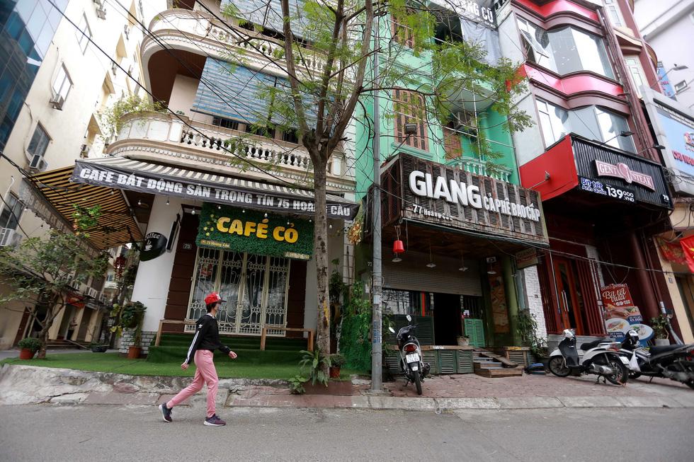 Đền chùa Hà Nội đóng cửa, người hành hương vái vọng, nhét tiền qua khe cổng - Ảnh 9.
