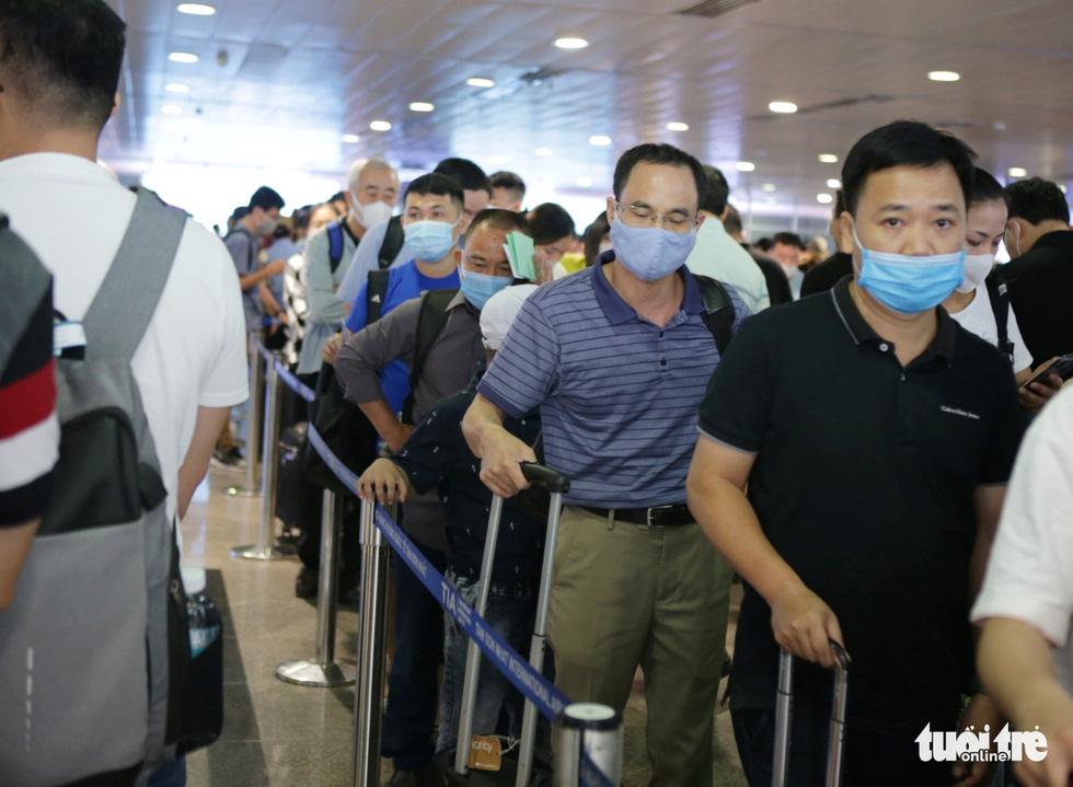 Hàng ngàn khách chen chúc chờ soi chiếu ở sân bay Tân Sơn Nhất - Ảnh 14.
