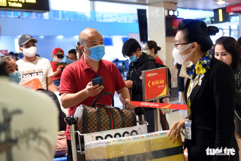 Hàng ngàn khách chen chúc chờ soi chiếu ở sân bay Tân Sơn Nhất - Ảnh 3.