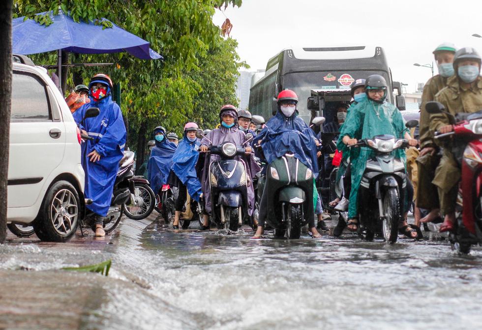 Đường Phạm Văn Đồng ngập, kẹt xe sau mưa lớn, CSGT phải moi rác cho nước chảy - Ảnh 5.