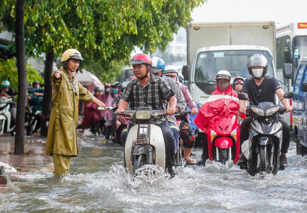 Đường Phạm Văn Đồng ngập, kẹt xe sau mưa lớn, CSGT phải moi rác cho nước chảy - Ảnh 3.