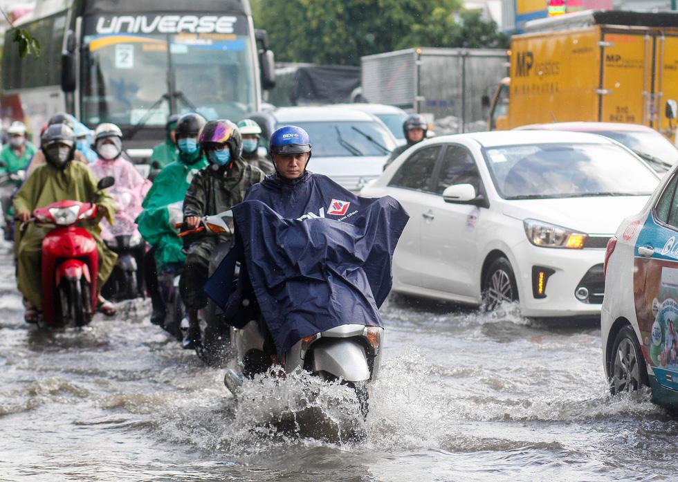 Đường Phạm Văn Đồng ngập, kẹt xe sau mưa lớn, CSGT phải moi rác cho nước chảy - Ảnh 2.