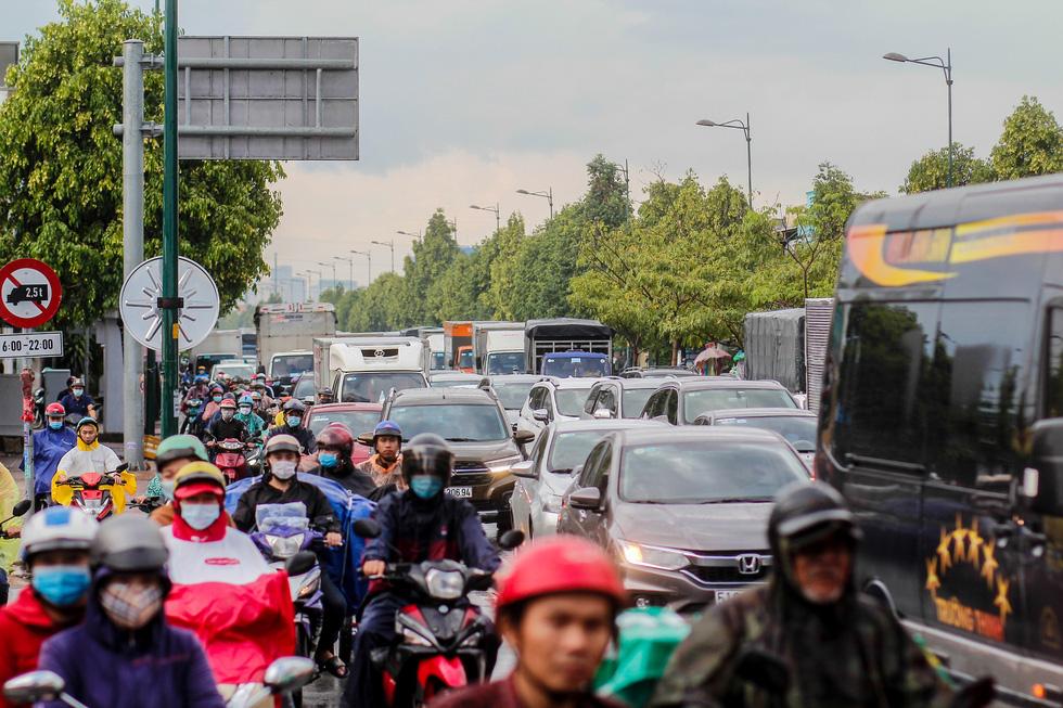 Đường Phạm Văn Đồng ngập, kẹt xe sau mưa lớn, CSGT phải moi rác cho nước chảy - Ảnh 6.