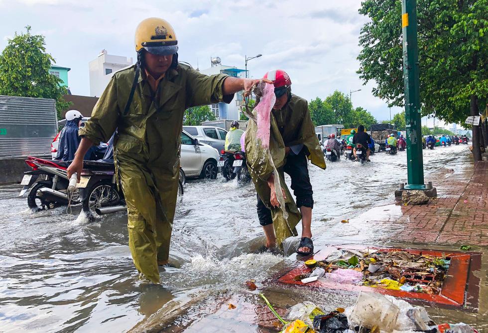 Đường Phạm Văn Đồng ngập, kẹt xe sau mưa lớn, CSGT phải moi rác cho nước chảy - Ảnh 1.