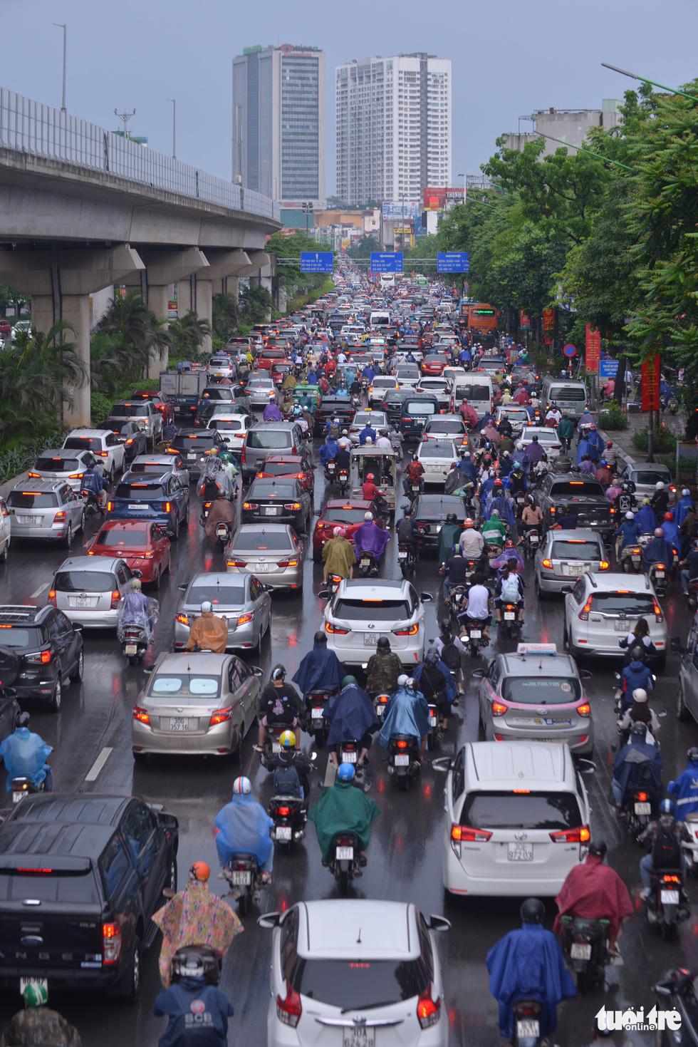 Ùn tắc khắp Hà Nội do mưa lớn, ban ngày nhưng trời tối đen như mực - Ảnh 3.
