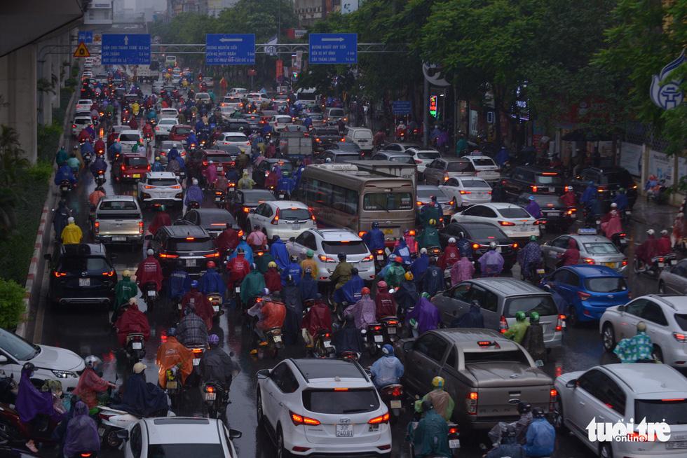 Ùn tắc khắp Hà Nội do mưa lớn, ban ngày nhưng trời tối đen như mực - Ảnh 1.