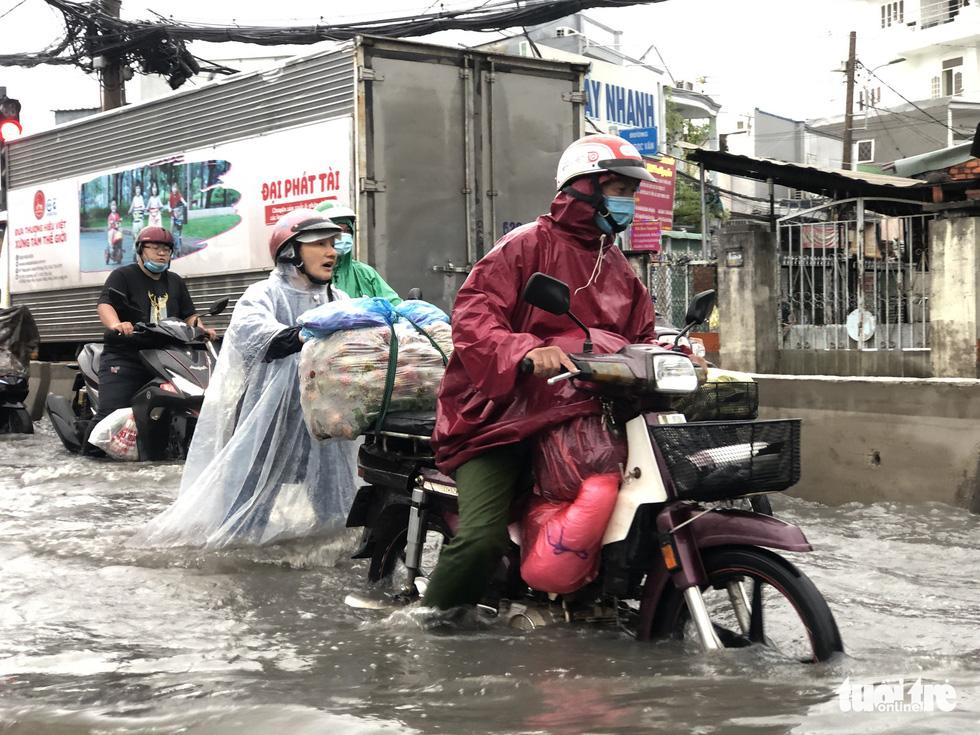 Mưa trắng trời, người dân TP.HCM lại lội nước giữa trưa - Ảnh 4.