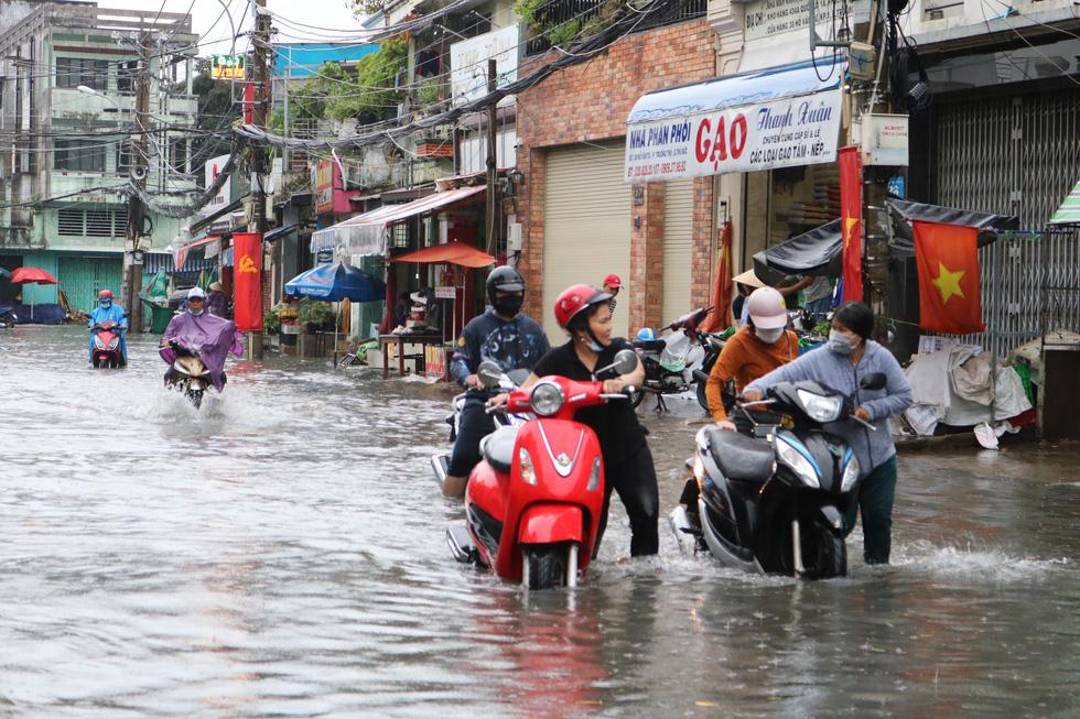 Mưa trắng trời, người dân TP.HCM lại lội nước giữa trưa - Ảnh 12.