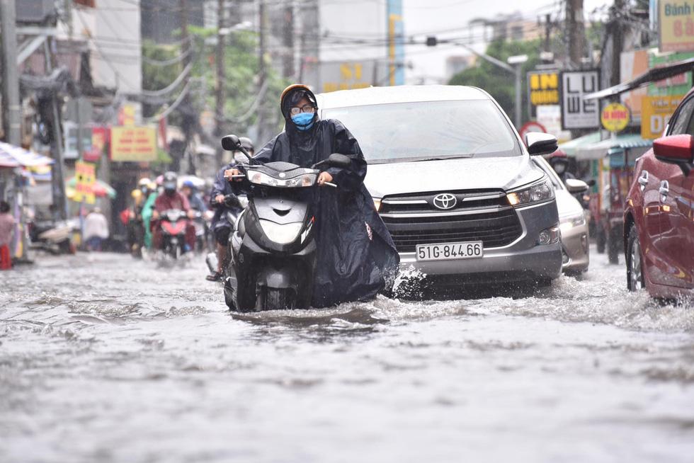 Mưa như trút suốt buổi sáng, dân Sài Gòn bì bõm dắt xe chết máy qua điểm ngập - Ảnh 1.
