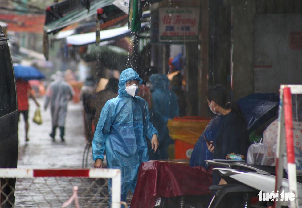 Dầm mưa khoanh vùng, truy vết người liên quan ca COVID-19 ở TP.HCM - Ảnh 1.
