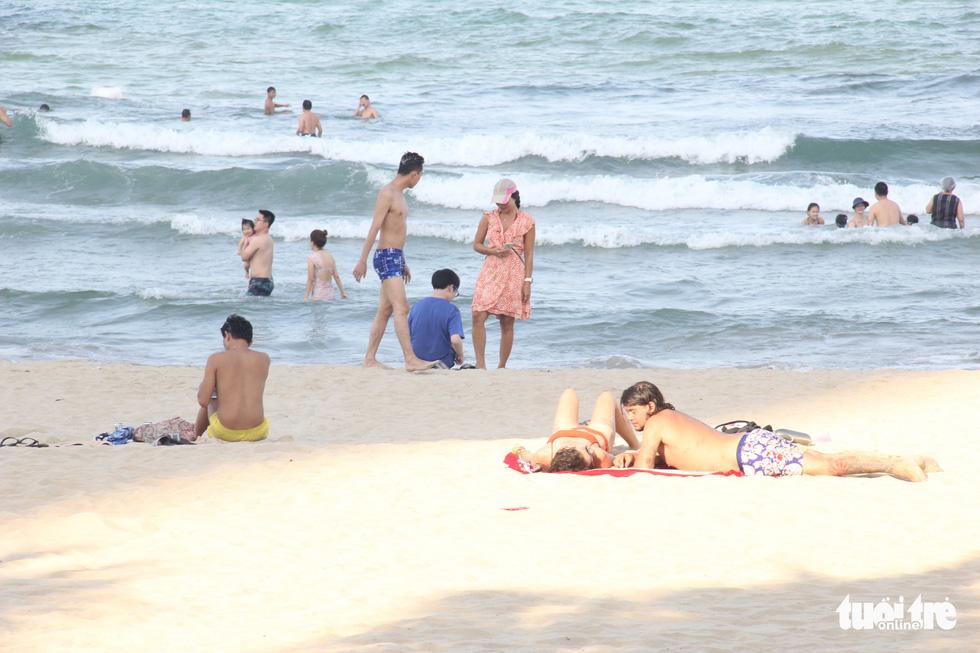Ngoài phố Đà Nẵng dân mang khẩu trang kín mít, ở biển nhắc mới đeo - Ảnh 4.