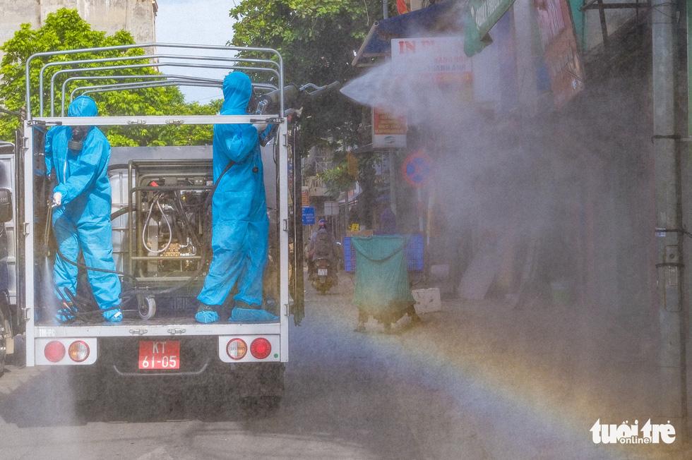 Phun khử khuẩn toàn bộ thị trấn Quốc Oai, Hà Nội vì chùm ca bệnh phức tạp - Ảnh 7.