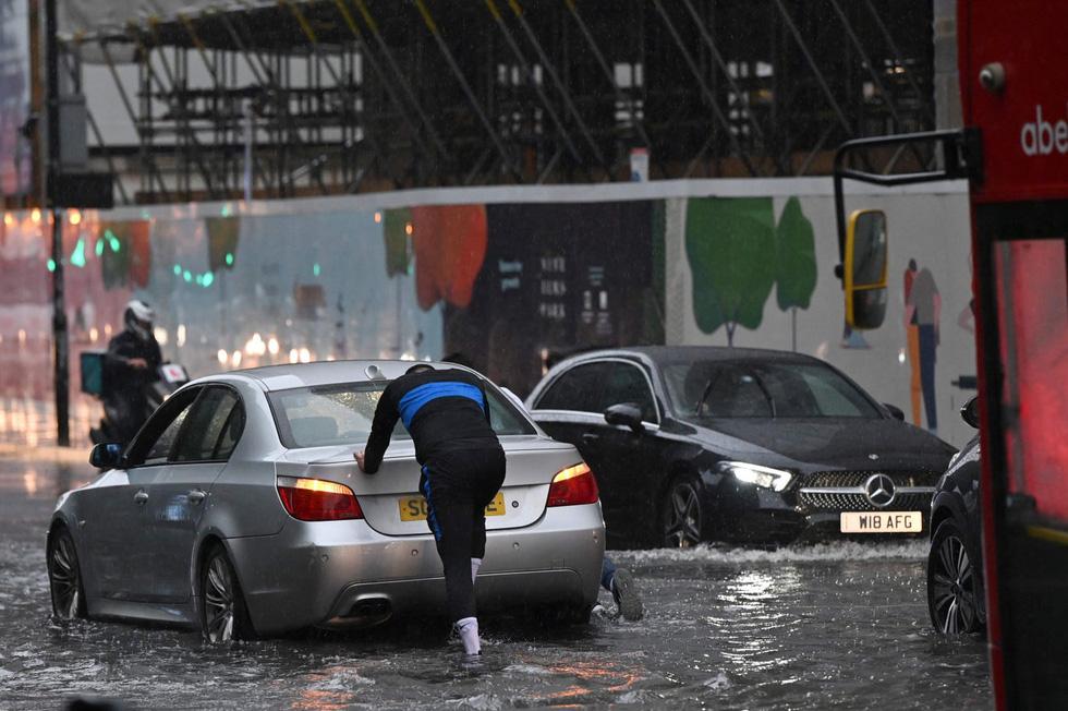 Mưa lũ bất thường biến nhiều con đường ở London thành sông - Ảnh 2.