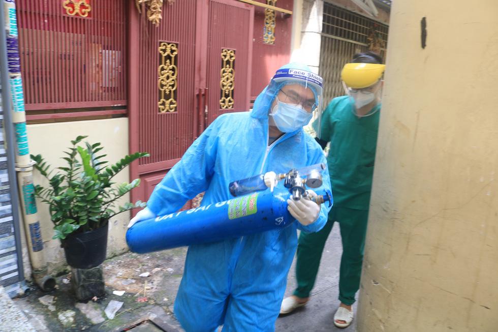 Bác sĩ quân y ôm bình oxy chạy trong hẻm nhỏ cấp cứu bệnh nhân F0 - Ảnh 2.