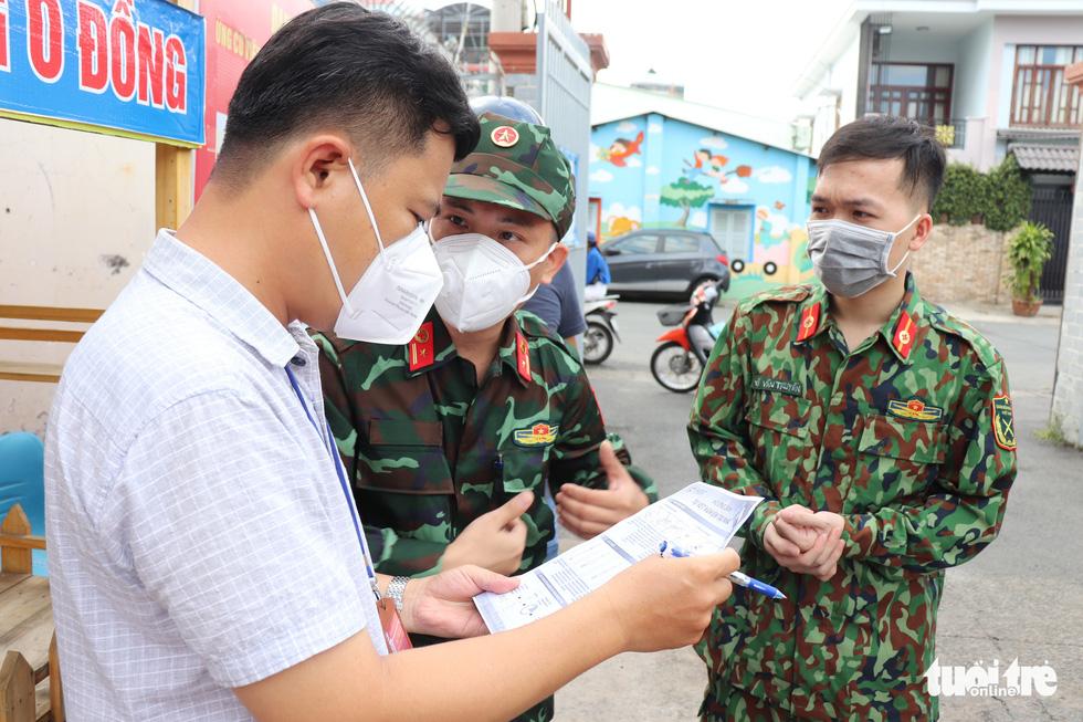 Khoác đồ bảo hộ, chiến sĩ Học viện Quân y tận tình hướng dẫn người dân TP.HCM test nhanh tại nhà - Ảnh 2.
