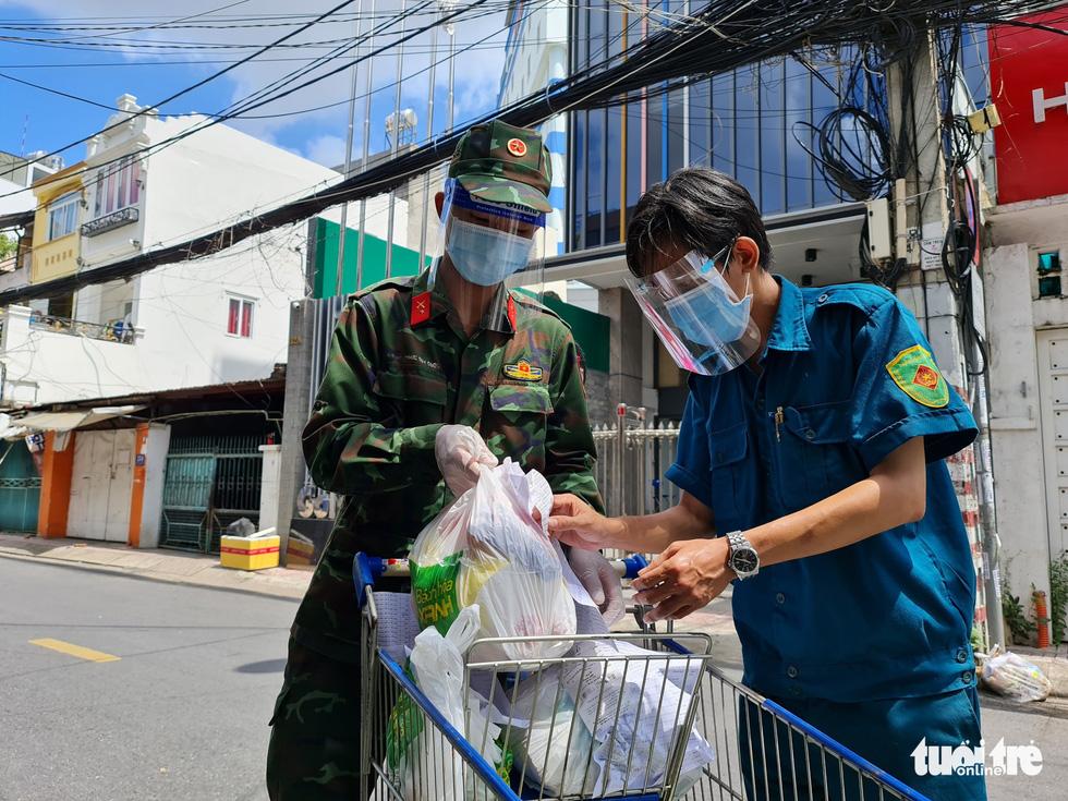Cán bộ phường, tình nguyện viên cùng đi chợ hộ, mang thực phẩm đến tận nhà dân - Ảnh 15.