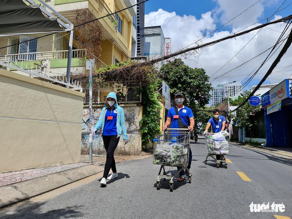 Cán bộ phường, tình nguyện viên cùng đi chợ hộ, mang thực phẩm đến tận nhà dân - Ảnh 14.