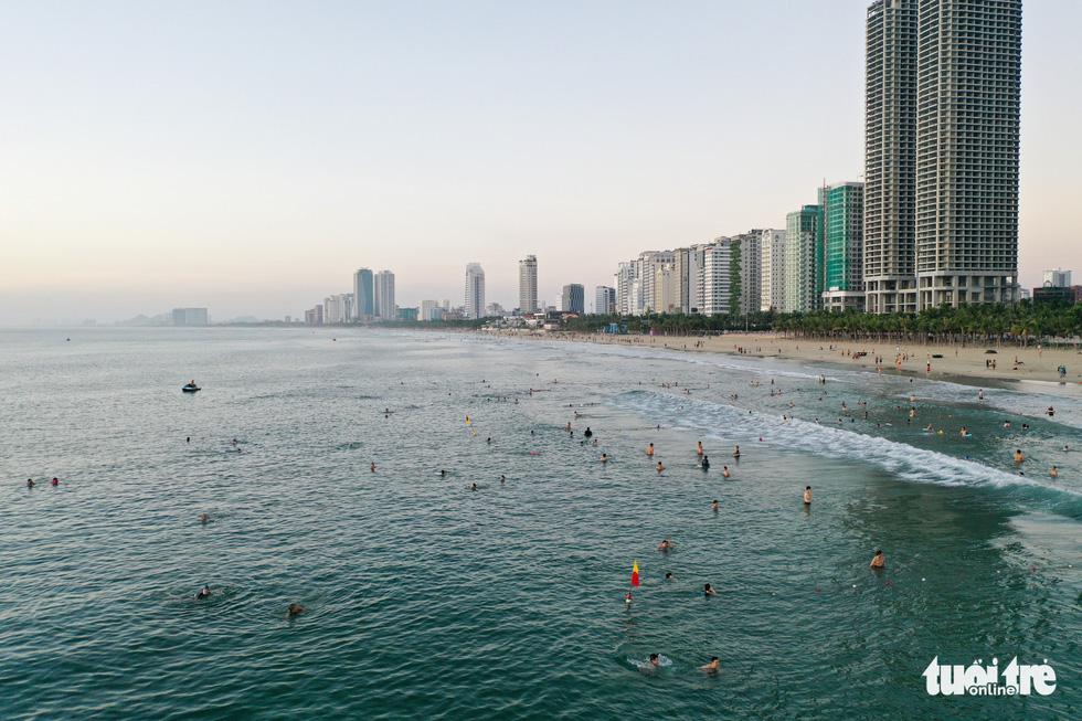 Người Đà Nẵng vui vẻ rủ nhau tắm biển sớm sau nhiều ngày giãn cách - Ảnh 2.
