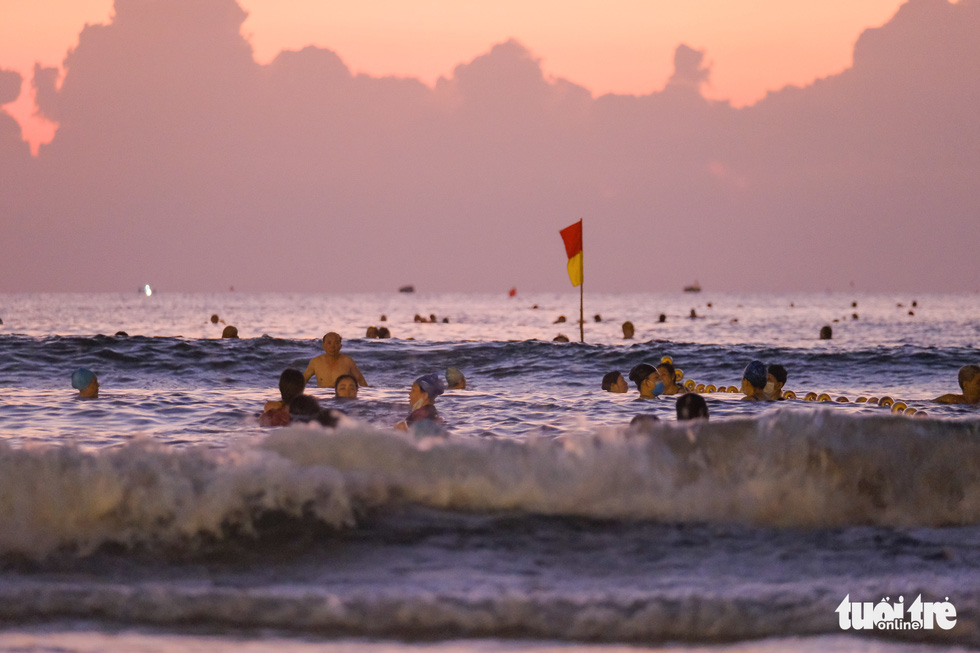 Người Đà Nẵng vui vẻ rủ nhau tắm biển sớm sau nhiều ngày giãn cách - Ảnh 1.
