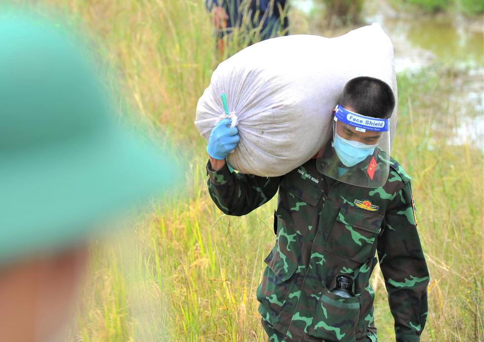 Bộ đội về thôn quê giúp nông dân vác lúa, bắt cá, giao sách giáo khoa cho học sinh - Ảnh 2.