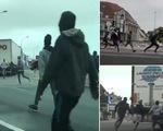 Sốc với cảnh rượt đuổi di dân bám đuôi xe container