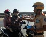 """CSGT TP.HCM """"thổi còi"""" người đi xe máy để... tặng nước suối, khăn lạnh trên đường về tết"""