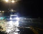 Nước lũ tràn qua quốc lộ 1 vào nhà dân, công an đội mưa điều tiết giao thông